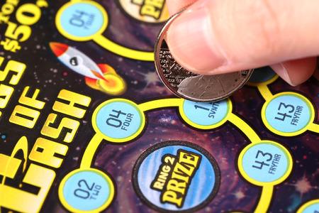 코퀴틀람 BC 주 캐나다 - 2015 년 3 월 21 일 : 여자 복권을 긁적. British Columbia Lottery Corporation은 1985 년 이후 브리티시 컬럼비아에서 정부가 허가 한 복권 게