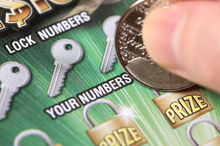 sanctioned: Coquitlam BC Canada - March 21, 2015 : Woman scratching lottery tickets. The British Columbia Lottery Corporation has provided government sanctioned lottery games in British Columbia since 1985.