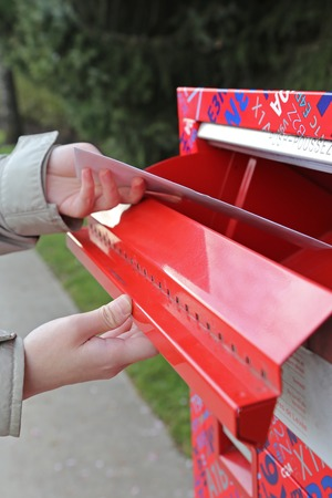 Hand sending a tax report letter in a red mail box Reklamní fotografie - 40954308
