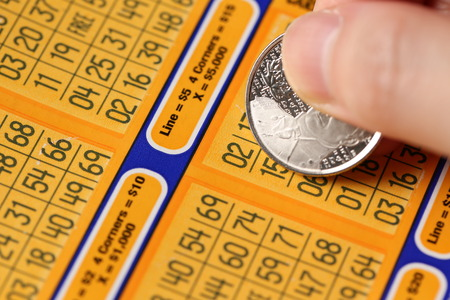 sanctioned: Coquitlam BC Canada - June 02, 2015 : Woman scratching lottery tickets. The British Columbia Lottery Corporation has provided government sanctioned lottery games in British Columbia since 1985.