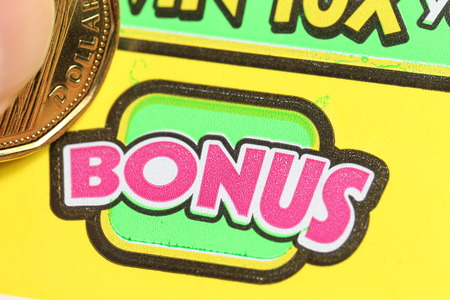 sanctioned: Coquitlam BC Canada - June 04, 2015 : Woman scratching lottery ticket on bonus section. The British Columbia Lottery Corporation has provided government sanctioned lottery games in British Columbia since 1985. Editorial