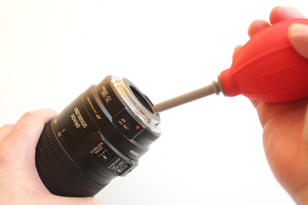 air pump: Using air pump to clean camera lens on white background
