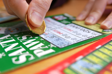 sanctioned: Coquitlam BC Canada - January 24, 2015 : Woman scratching lottery tickets. The British Columbia Lottery Corporation has provided government sanctioned lottery games in British Columbia since 1985. Editorial