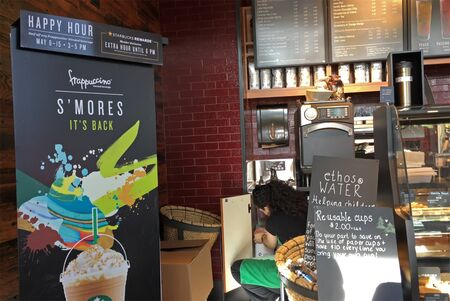 Worker stocking cups with display happy hour sale sign inside Starbucks coffee