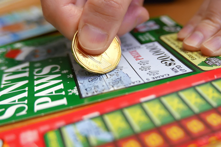 Coquitlam BC Canada - January 24, 2015 : Woman scratching lottery tickets. The British Columbia Lottery Corporation has provided government sanctioned lottery games in British Columbia since 1985. Editorial