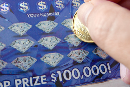 sanctioned: Coquitlam BC Canada - June 04, 2015 : Woman scratching lottery ticket The British Columbia Lottery Corporation has provided government sanctioned lottery games in British Columbia since 1985.