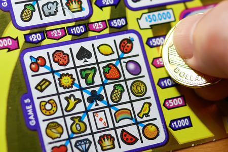 sanctioned: Coquitlam BC Canada - October 31, 2016 : Man scratching lottery ticket. The British Columbia Lottery Corporation has provided government sanctioned lottery games in British Columbia since 1985. Editorial