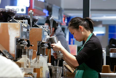 Burnaby, BC, Canada - March 07, 2017 : Motion of barista making coffee for customer at Starbucks store