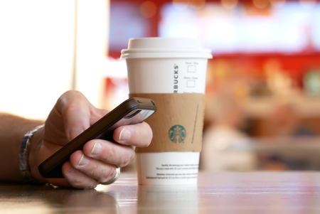 Burnaby, BC, Canada - May 04, 2017 : Man reading message on his phone and drinking Starbucks hot beverage coffee with blur motion people at food court area