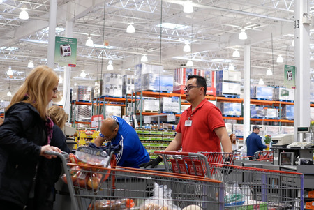 Port Coquitlam, BC, Canada - April 11, 2017 : Motion of cashier scanning food and stocking them on trolley at check out counter inside Costco