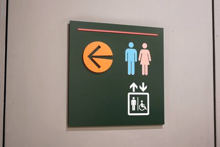 Close up man, woman and disable washroom  on wall Banco de Imagens