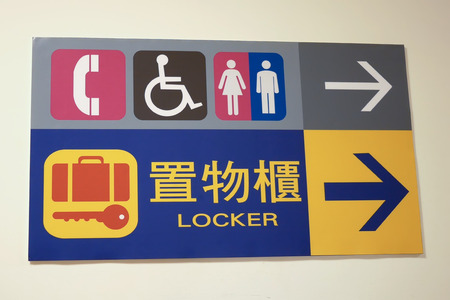 Close up man, woman disable washroom and locker logo on wall Stock Photo