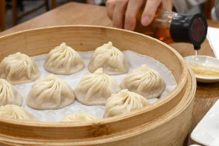 People pouring vinegar before eating soup dumpling buns in restaurant Stock Photo