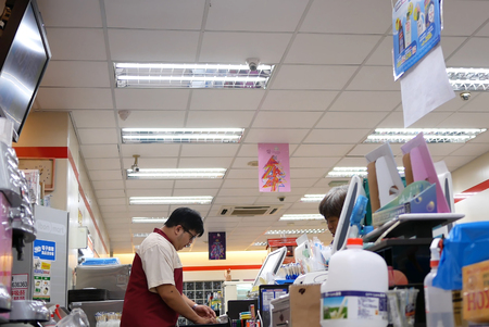 Taipei, Taiwan - October 25, 2017 : People paying food at 7-11 check out counter in Taipei Taiwan