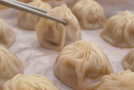 Motion of woman eating soup dumpling buns with chopsticks inside restaurant in Taipei Taiwan