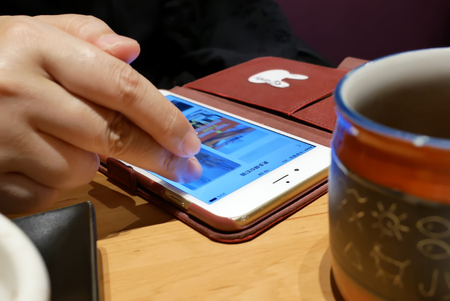 Taipei, Taiwan - August 25, 2018 : Motion of people browsing photo on iphone inside a Japanese restaurant