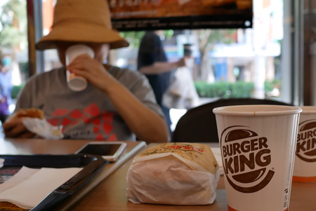 Taipei, Taiwan - August 17, 2018 : Blur motion of woman eating burger and drinking hot coffee at Burger King fast food restaurant