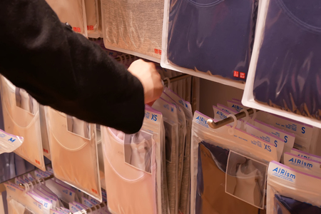 Coquitlam, BC, Canada - March 20, 2019 : Motion of woman buying clothes inside uniqlo store