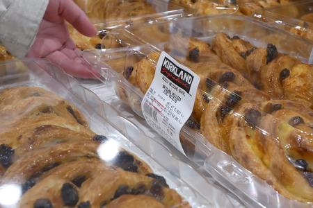 Coquitlam, BC, Canada - February 20, 2019 : Motion of people buying raisin brioche swirl inside Costco store