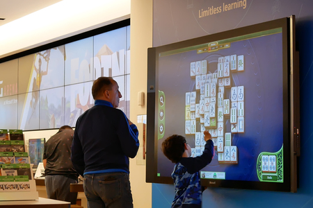 Coquitlam, BC, Canada - March 31, 2019 : Motion of father and children playing xbox game on tv screen at Microsoft store Editoriali