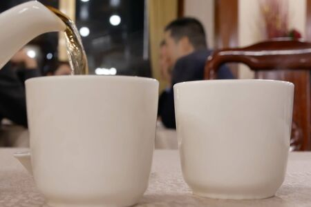 Motion of people pouring hot tea inside Chinese restaurant Archivio Fotografico