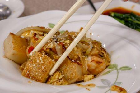 Motion of people eating pan fried turnip cake dim sum inside Chinese restaurant