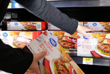 Motion of woman buying great value beef burgers inside Walmart store Archivio Fotografico - 133174318