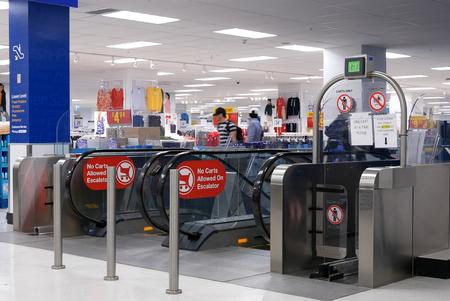 Motion of people taking escalators in modern urban interior inside Walmart store Archivio Fotografico - 133174323
