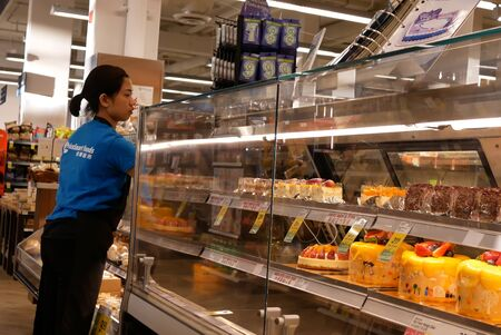 Burnaby, BC, Canada - May 09, 2019 : Motion of worker cleaning display cake rack at dessert section inside price smart foods store Archivio Fotografico - 137901185