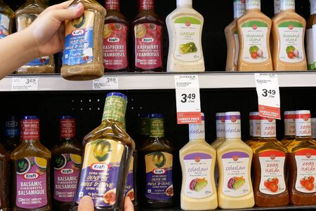 Burnaby, BC, Canada - May 09, 2019 : Motion of people comparing two different olive oil dressing inside price smart foods store Archivio Fotografico - 137901188