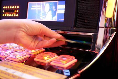 Coquitlam, BC, Canada - May 31, 2019 : Motion of woman inserts money on slot machine inside Casino Archivio Fotografico - 137901203