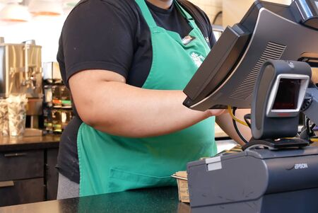 Burnaby, BC, Canada - March 26, 2019 : Motion of barista taking order for customer at store Archivio Fotografico - 137901204