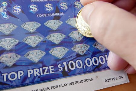 Close up man scratching diamond lottery ticket Archivio Fotografico - 144337983