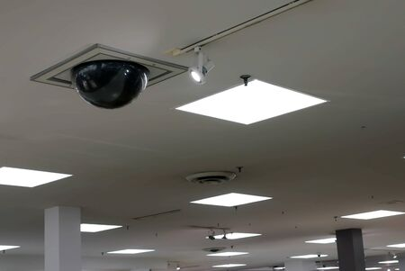 Dome security camera on top of ceiling inside Sears store