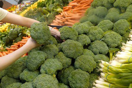 Woman selecting broccoli in grocery store Archivio Fotografico - 143277607