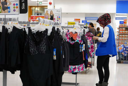 Worker checking price tag for display clothes on sale inside Walmart store Archivio Fotografico - 144363098