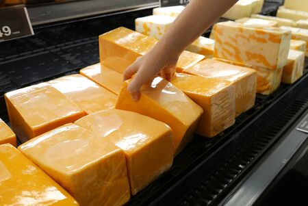 Motion of woman's hand picking cheese inside superstore Stock Photo
