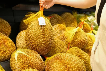 Motion of woman's hand picking durian inside superstore Archivio Fotografico - 147603906