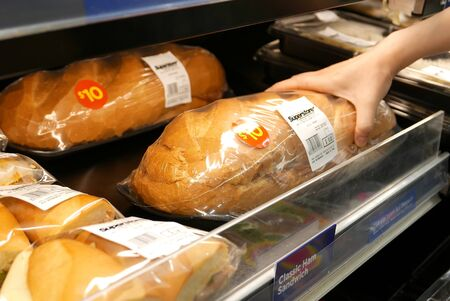 Motion of woman's hand picking big sandwich inside superstore Archivio Fotografico - 147603860