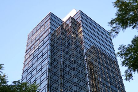 Motion of blue sky with illuminated reflected glass facade on modern office building Archivio Fotografico - 147603871