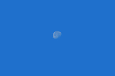 waning moon: Waxing Moon Phase, highly detailed half moon against a bright blue daytime sky Stock Photo