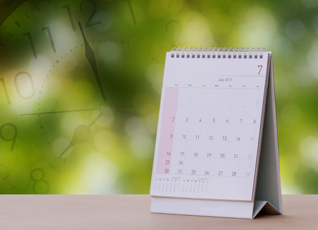 calendario julio: July Calendar 2017 with Clock Screen on wood table with Beautiful Nature Bokeh.Blurred background  Foto de archivo