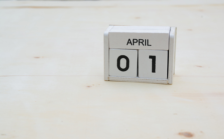 april 1 wood cube calendar on wooden table with copy space