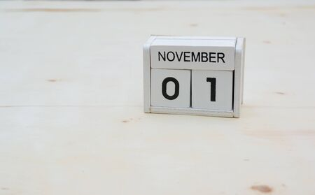 1 november wood cube calendar on wooden table with copy space