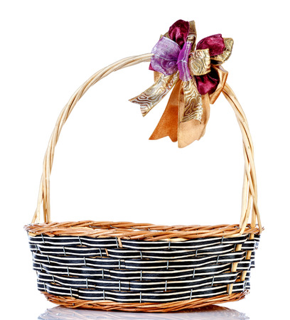 Empty wicker basket with ribbon isolated on white background photo