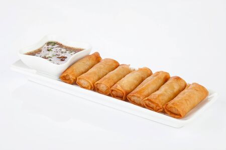 sweet and sour: crispy spring rolls on white dish with Sweet & Sour Sauce.