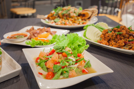 Spicy salmon salad with mixed vegetable and grill pork and spicy crispy pork Stock Photo