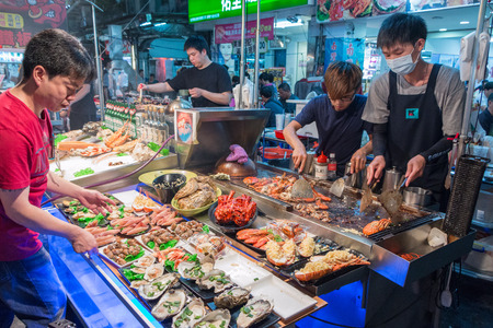 KAOHSIUNG, TAIWAN - APR 20 : Chief prepares seafood to be sold in Kaohsiung night market on April 20, 2015. People enjoy food at night market in Taiwan. And is one of the unique culture in Taiwan. Editorial