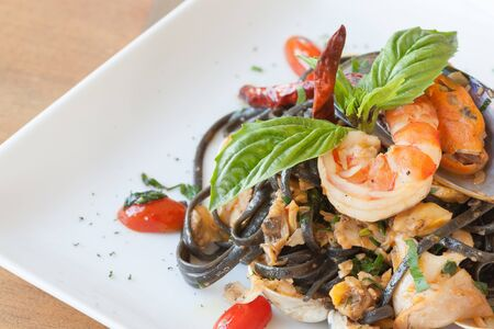 tomate: Black spaghetti with seafood on white dish.