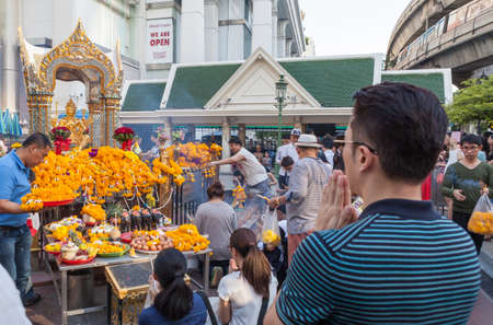 phrom: BANGKOK, THAILAND - SEPTEMBER 26, 2015: People are paying respect to the Erawan Shrine, which is a Hindu shrine housing a statue of Phra Phrom, the Thai representation of the Hindu creation God Brahma